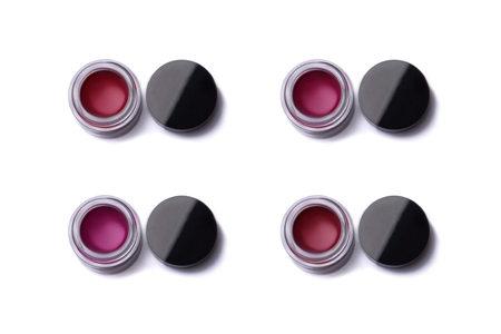 glosses: Red shade lip glosses in jars, top view isolated on white background