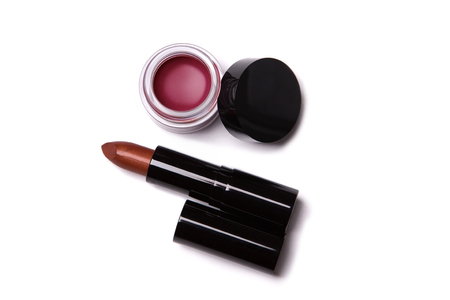 beauty products: Top view of metallic red lipstick and lip gloss in jar, isolated on white background