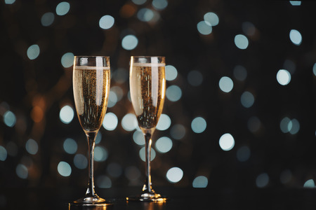 glass background: Two champagne glasses over dark bokeh background