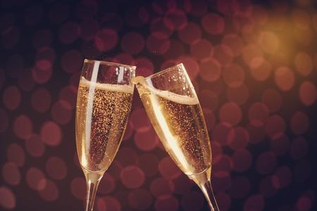 brindisi spumante: Due bicchieri di champagne elegante toast su sfondo bokeh di vacanza