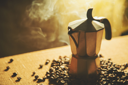 italian: Artistic shot of old coffee maker and coffee beans, shot on canvas background Stock Photo