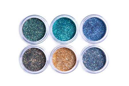 eyeshades: Bright cosmetic glitters in transparent jars, top view isolated on white background