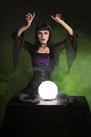 erotic fantasy: Beautiful fortune teller wearing gothic style outfit, Halloween setting with crystal ball