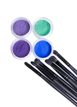 Set of bright mineral eye shadows and makeup brushes, top view isolated on white background Stock Photo