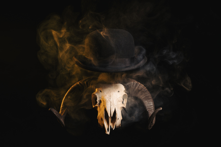 Ram skull with horns in a bowler hat, Halloween theme Фото со стока
