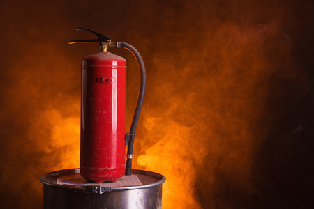 Fire extinguisher on bright orange smoky background Фото со стока