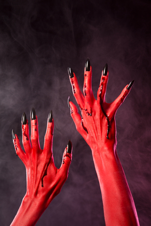 Red devil hands with black nails covered in blood, Halloween theme
