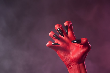 Red devil hand with black glossy nails, Halloween theme