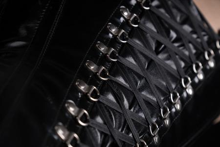 Close-up shot of black fetish corset lacing  Фото со стока