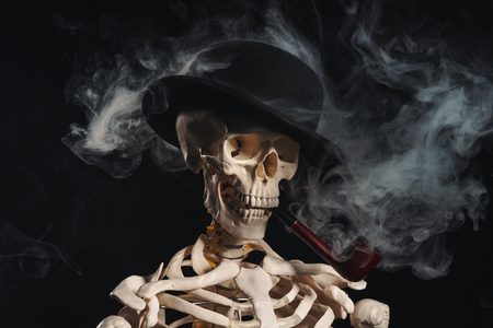 Skeleton in bowler hat with pipe, smoking kills concept
