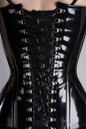 Achteraanzicht van sexy fetish vrouw in zwart glanzend korset