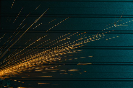 Close-up shot of angle grinder sparks over urban background  Фото со стока