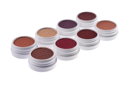 Studio shot of eye shadows in brown and red colors, isolated on white background