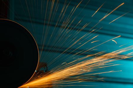 Angle grinder with bright sparkles over metal background