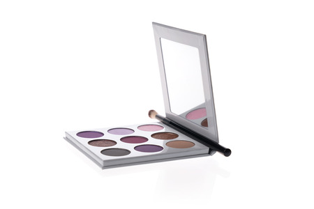 Eye shadow palette in purple colors with a mirror, isolated on white background