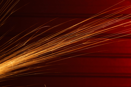 Angle grinder sparks, indoors shoot over red metal background  Фото со стока