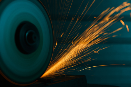 Close-up shot of an angle grinder with sparkles over metal background