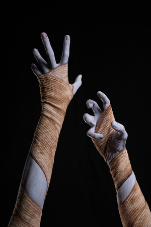 Spooky mummy stretching up hands wrapped in bandages, Halloween Фото со стока