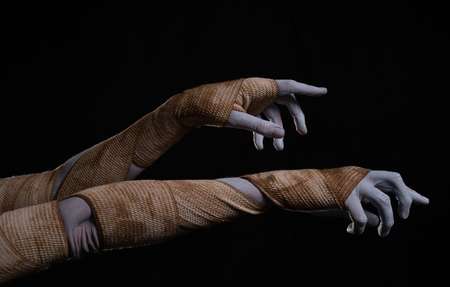 Creepy mummy stretching hands wrapped in bandages, Halloween theme