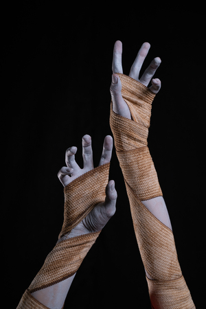 Mummy stretching up hands wrapped in bandages, Halloween theme Фото со стока