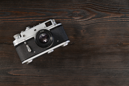 High angle view on a vintage camera on a grungy wooden background Фото со стока