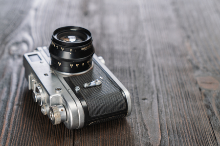 Closeup shot of a camera on a grungy wooden background, selective focus