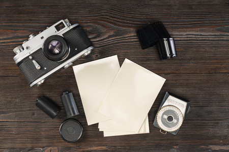 High angle view of a vintage camera, film, photo paper and light meter