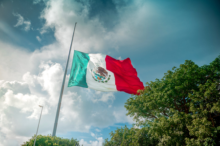 yucatan: Giant mexican flag flies in the wind in Cancun. Shot in Yucatan, Mexico