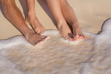 Two pairs of legs on white sand Фото со стока