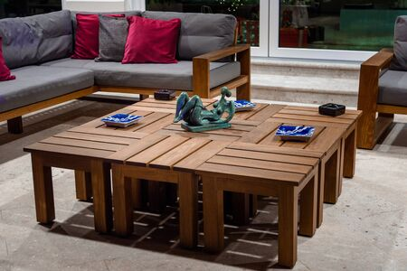 Wooden table with plates and sculpture in the patio