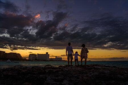 Silhouette of a family holding sunset on the beach