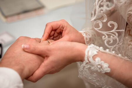 Hands of the newlyweds at the wedding ceremony of dressing the wedding rings, hands close-up. Фото со стока