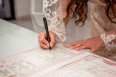 The bride signs the certificate of marriage. Reklamní fotografie