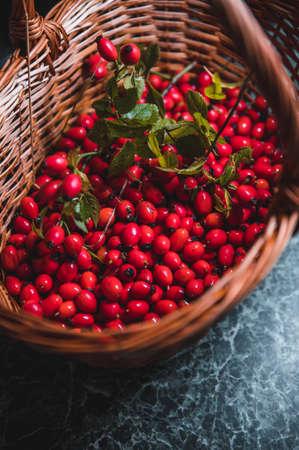 Dark red rose hip on basket Stock Photo