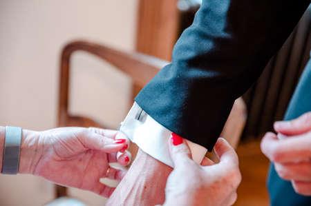 Preparation of groom, cufflinks on shirt.
