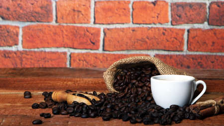 White Hot Coffee cup with Coffee beans, burlap sack and with cinnamon sticks on the wooden table Banque d'images