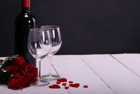 Happy Valentines Day with red wine, red roses, wine glasses, white background and hearts in love Stock Photo