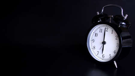 Close up image of old black vintage alarm clock. Time management and deadline urgency concept. Six o'clock