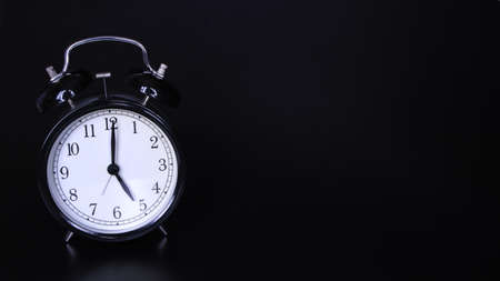 Close up image of old black vintage alarm clock. Time management and deadline urgency concept. Five oclock