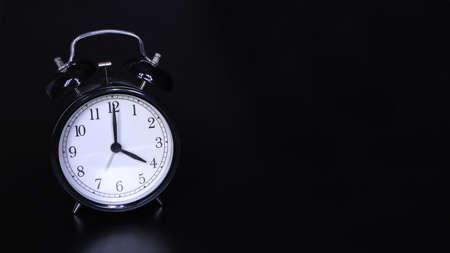 Close up image of old black vintage alarm clock. Time management and deadline urgency concept. Four oclock