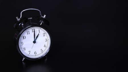 Close up image of old black vintage alarm clock. Time management and deadline urgency concept. One o'clock