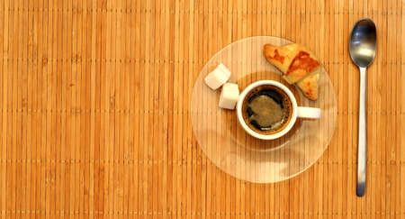 Croissant and a cup of coffee on a plate