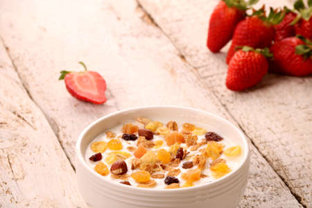 Bowl of yogurt with strawberries and granola muesli, over a white rustic wood background. Stockfoto