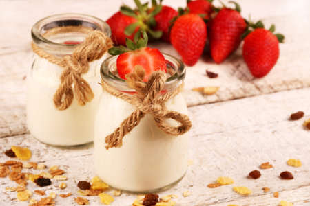 Jar with delicious yogurt and strawberry and granola muesli, over a white on wooden table