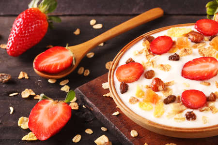 Bowl of yogurt with strawberries and granola muesli, over a white wood background. Stock fotó