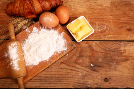 Kitchen rolling pin, wooden bowl with flour on rustic wooden background and butter for making croissant on table.