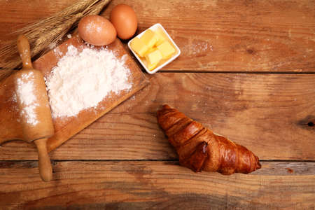 Kitchen rolling pin, wooden bowl with flour on rustic wooden background and butter for making croissant on table. Stock Photo