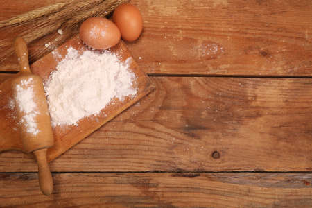 Kitchen rolling pin, wooden board with flour on rustic wooden background ears and eggs for making bread on table.
