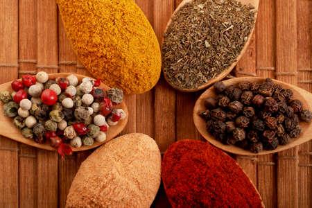 Gruppe indischer Gewürze und Kräuterunterschiede in Holzlöffeln auf Holzhintergrund mit Draufsicht und Kopienraum für Designlebensmittel, Gemüse, Gewürze, Kräuter, gesunde Lebensweise oder andere Inhalte. Standard-Bild