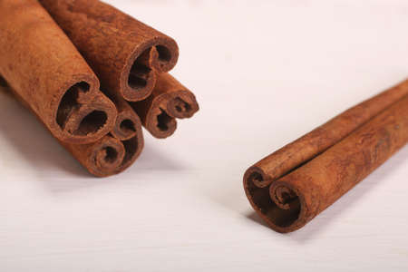 Ground cinnamon, cinnamon sticks, tied with jute hempen rope on wooden white background, selective soft focus